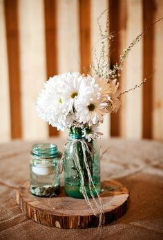 Budget centerpieces  My comment: like the wood idea but maybe gloss it so its shines, them do lace and burlap on jars instead of twine, and last make my bouquet stunning and full and then make girls bouquets the same flowers for the tables. Then use the three bridesmaids and maid of honor bouquets on their table. Order more for reception.
