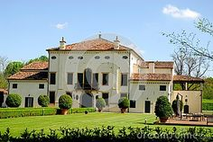 Photo taken in mid-April, close to Limena on the outskirts of Padua in Veneto Italy. In the picture you see the facade of a beautiful villa. In the foreground you see the green lawn and the driveway to the villa bordered by two box hedges and some small plants. The light color of the villa is well suited to the green grass and the blue of the sky.