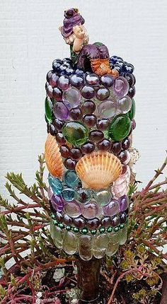 Glass bottle turned upside down and covered in mosaics
