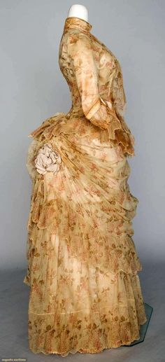 "PRINTED TULLE BUSTLE DRESS, 1886 cream cotton tulle printed w/ small sprays of rose colored flowers & green leaves, a-symmetrically draped skirt w/ ribbon rosettes, petersham label ""C. 1880s Fashion, Edwardian Fashion, Vintage Fashion, Vintage Couture, Vintage Outfits, Vintage Gowns, Historical Costume, Historical Clothing, Historical Dress"
