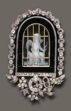 A CHARMING ANTIQUE AGATE AND DIAMOND BROOCH, BY TIFFANY & CO. Centering upon a carved agate cameo depicting a seated angel, locked behind gold bars, within a rose and old mine-cut diamond chain link surround, the base enhanced by a similarly-set key and foliate motif, mounted in gold, circa 1890, in a Tiffany & Co. red leather case With jeweler's mark for Tiffany & Co.