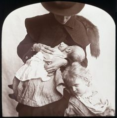 1910, Mother feeding baby, with young child.