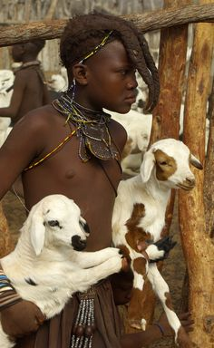 Africa | A Himba child carrying two goats.  Kunene region, Namibia | ©Thomas J Michel