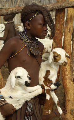 Africa | A Himba child carrying two goats.  Kunene region, Namibia | ©Thomas J Michel