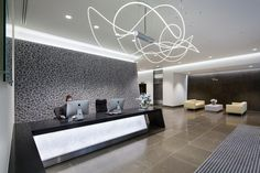 This reception includes bespoke stone walls & tiling, a polished concrete desk & a stunning feature light