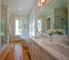 Modern Small Bathroom Idea with Wooden Flooring and White Cabinetry Design Flat Huge Mirror also Double White Washbasin Flat Chrome Double Faucets also Hidden Ceiling Lights and Bathtub