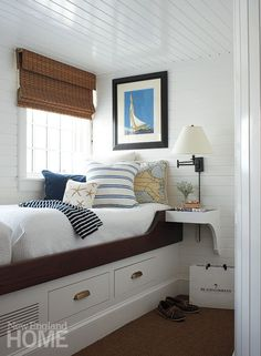 A nautical nook makes smart use of space with built-in drawers, a floating bedside table, and a wall mounted lamp.