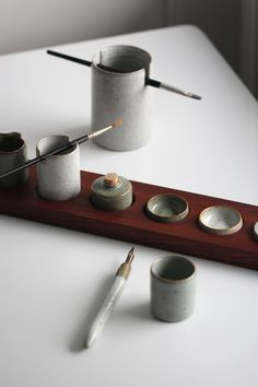 Watercolour palette with a collection of pots with the intent of painting and drawing. Crackle glazes and mahogany.