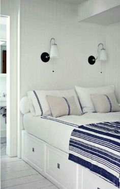 bedroom - storage bed, sconce lights on wall over pillows