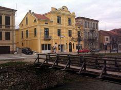 Gjurmë të garfiteve antishqiptare në një fasadë që ka filluar të rrënohet, dyqane për artikuj sanitarë dhe një oborr i papastruar për një kohë të gjatë.
