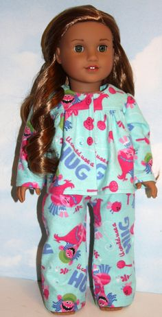 Your doll will enjoy watching her favorite movie in these soft and cozy flannel pajamas featuring a cute print of pink and purple troll characters ready to give someone a hug. The long sleeve top has a gathered front and back yoke and three decorative bright pink oval buttons down the front; closes with Velcro. The elastic waist flannel pants make dressing easy for little hands. Made by me in my smoke-free, pet friendly home using a Little Abbie pattern. All seams are serged/finished to ...