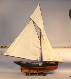 "Large vintage pond yacht model rigged with a full suit of sails. Scribed and varnished deck. Many brass fittings. 69"" long x 12"" wide x 81"" tall"