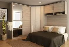 Habitación de matrimonio con armario en esquina y zona de almacenaje encima del cabecero de la cama... todo ello a base de módulos.