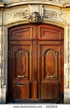 Classic wooden door with bronze handles in Paris by Vladislav Gurfinkel, via Shutterstock