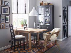Ein Esszimmer mit MÖCKELBY Klapptisch in Eiche, zwei Stühlen in Schwarzbraun und einem Rattansessel, im Hintergrund ein schwarzbrauner Vitrinenschrank
