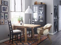 Ruokailutila, jossa tamminen kuuden istuttava klaffipöytä, kaksi mustanruskeaa tuolia, korituoli ja mustanruskea vitriinikaappi.