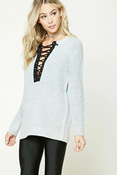 A soft marled knit sweater featuring a lace-up front with grommets, split neckline, long dropped sleeves, and a ribbed trim.