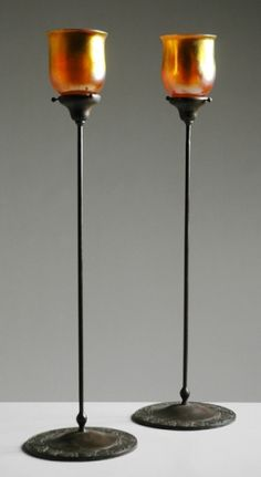 Pair of Tiffany Style Bronze and Gold Iridescent Glass Candlesticks  Each of floriform, with a bell-shaped shade in translucent amber glass with brilliant gold iridescent finish, supported on a tall thin straight standard decorated with a meandering vine and berry cluster motif. Glass Candlesticks, Antique Lighting, Amber Glass, Decorative Objects, Iridescent, Berry, Tiffany, Bronze, Shades