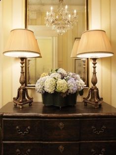Classic set up for an entry table - large mirror, two lamps, and some greenery.