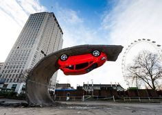 Car upended on tarmac wave in Alex Chinneck installation.