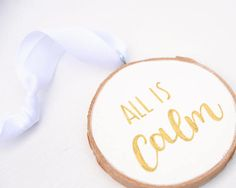 All is Calm Christmas ornament, hand lettered in metallic gold on white, painted on a birch wood slice. The reverse side is left as blank, natural wood. This ornament has a modern rustic style, and could be a great addition to your holiday decor. Hang it on your Christmas tree or display on a festive mantle. It would even make a fabulous gift tag! Give it as a unique and interesting gift, perfect for a Christmas stocking filler or party favour.   Each ornament is hand-painted with love, and…