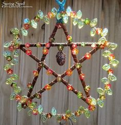 Spring Spell. Ostara pentacle with willow branches, copper wire, glass flowers, glass leaves, and brass egg-shaped locket. Use the locket to hold herbs, stones, thoughts, or scrolls of paper.