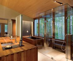 Everything you need in a beautiful bathroom with wooden style. Deep soaking bath and two person walk in glass shower with huge square shower overhead