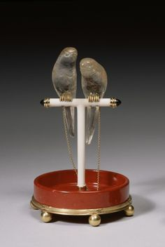 A pair of topaz parakeets with peridot eyes and gold feet is perched on a T-shaped ivory stand and connected by gold chains to the mount. The cross bar of the stand terminates in cabochon sapphires. The high rimmed, purpurine feeding tray rests on a fluted gold base supported by six gold balls.
