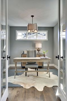 Transitional design, modern furnishings, wood desk, layered rug, cool palette