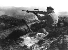 A Canadian member of the joint American-Canadian landing force squints down the sights of a Japanese machine gun found in a trench on Kiska Island, Alaska, on August 16,...