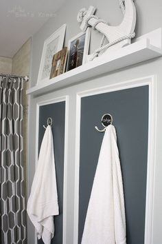 This feature wall in the bathroom uses hooks instead of a towel bar and I like the picture ledge above them