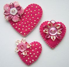 A set of three handmade felt heart brooches.... with beading button and ribbon details.