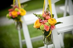 Looking for a unique color combination? Why not consider coral and yellow. This color combination is powerful, bright, happy, and still very elegant.  The brides bouquet was created with coral peony, green viburnum, mini green hydrangea, yellow billy balls, yellow freesia, yellow cabbage roses, coral colored spray roses, and yellow billy balls. Super sexy!!! Maids …