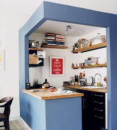 Dans ce petit appartement, le coin cuisine s'affiche dans son cube bleu ciel. Deux plans de travail se font face, et on a évité les meubles fermés en partie haute du mur, afin de ne pas surcharger l'espace.