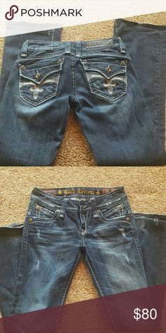 Rock revival jeans In excellent condition. Dark wash. Back flap pockets with bling buttons. Has distressed loom on front. Very cute! Size 28x32 Rock Revival Jeans Boot Cut