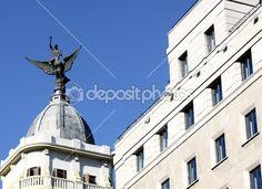 die Figur eines Engels auf ein weißes Gebäude mit einem blauen Himmel in madrid