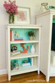 How effective does this coastal bookcase look! Painting the back board in a sea inspired color looks awesome!