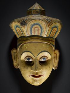 Mask used in the Sinhalese mask play, kolam, the yellow colour with red, green and black represent a merchant or high-ranking figure, carved Kaduru wood (Strychnos nux vomica): Sri Lanka, early - mid 19th century © National Museums Scotland