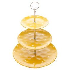 """Three-tier stoneware cake stand with a polka dot motif in yellow.  Product: Cake standConstruction Material: Stoneware and metalColor: YellowFeatures:  Displays cupcakes, muffins or scones on brightly colored plates with white polka dotsThree tiered stand Dimensions: 10"""" Diameter Cleaning and Care: Hand washing recommended"""