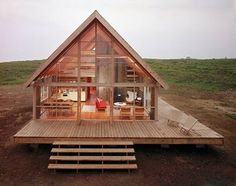 An open concept small house with a 2 or 3 sided deck. The windows would allow a lot of light and warmth in, assuming they are facing south.