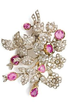 Antique Diamond and Pink Sapphire Flower Brooch. Silver, gold, the flower blossom and spray of florets and leaves embellished with 7 pear-shaped, oval and round pink sapphires, set throughout with numerous old-mine and rose-cut diamonds.