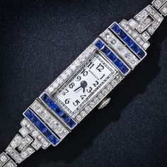 This fabulous platinum Art Deco bracelet watch, retailed in the 1930s by San Francisco's preeminent jeweler at the time - Shreve & Co. features a rectangular dial with Arabic numerals. The case and band are enhanced by 158 high-quality diamonds totaling 4.00 carats. Four bands of electric blue original synthetic sapphires border a row of square-cut diamonds adding a splash of striking sophistication to the design. The bracelet fastens securely with a box clasp and safety latch.