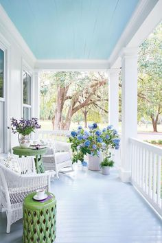 Blue hydrangeas look gorgeous underneath a porch ceiling painted in a clear, classic blue.
