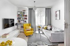Niezwykle modny duet szarego z żółtym świetnie skomponował się z paskami na dywanie. Piękny, żółty fotel - uszak będzie wspaniałym miejscem odpoczynku z ulubioną książką. Towarzyszy mu okrągły, błękitny stolik kawowy, który ładnie komponuje się z szarą sofą.