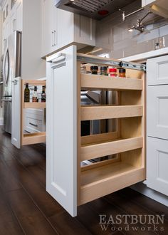 White Kitchen cabinets with pull-out spice drawers and #TopKnobs hardware