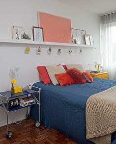 No quarto do casal, um carrinho e um antigo móvel pintado de amarelo ladeiam a cama. Acima, na parede, uma canaleta de MDF com cabo de aço, feita sob medida, é boa solução para pendurar fotos e expor quadros. Projeto da designer de interiores Renata Paras