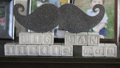 Spray painted wooden letter blocks and cardboard mustache