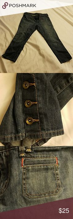 Tommy Hilfiger Crop Jeans Size 8 Mide Rise Tommy Hilfiger Jeans American Spirit  Mid Rise Medium to Dark Blue waist measures 34 along top seam 25 inch inseam 3 Tommy buttons on bottom of each leg Great Condition...left side of back is starting to wear but is still intact Tommy Hilfiger Jeans Ankle & Cropped