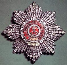 "Star of The Order of St. Catherine.  In gold around it reads (in Russian) ""For Love, and for Fatherland.""  Empress Alexandra and all four of the Grand Duchesses took their sashes with the badges and stars with them into exile in Siberia.  They were recovered in 1933. The Empress is the Grand Mistress for life.  Therefore, the Dowager Empress Marie who escaped the Revolution with her life was the Grand Mistress."