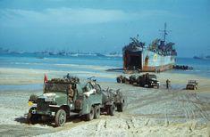Unloading vehicles and supplies from an LST (landing ship, tank) at Normandy beachhead, summer 1944.